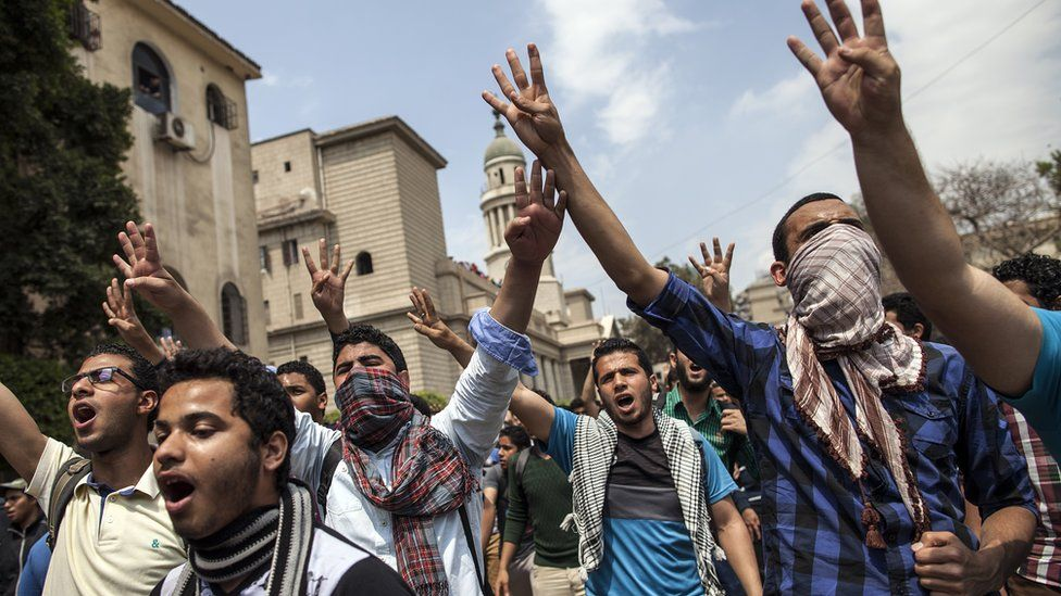 "Egyptian students, supporters of the Muslim Brotherhood and Mohammed Morsi, flash the four-finger ""Rabaa"" symbol, as they demonstrate outside Cairo University on 9 April 2014"