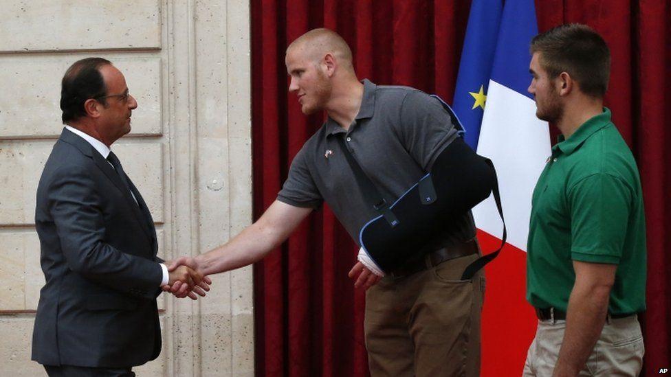 President Hollande shakes the hand of Spencer Stone, as Alek Skarlatos looks on, 24 Aug