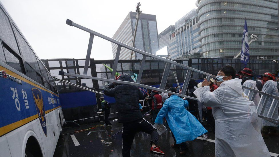 A protester hits a police bus with a ladder during the demonstration
