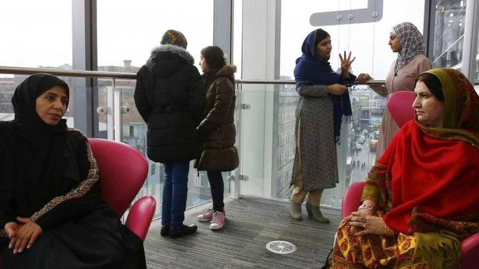 Malala Yousafzai (3rd on the right) speaks to 17-year-old Syrian refugee Muzoon Almellehan as their mothers Eman Almellehan (left) and Torpekai Yousafzai (right) speak at the City Library in Newcastle Upon Tyne (22 December 201)