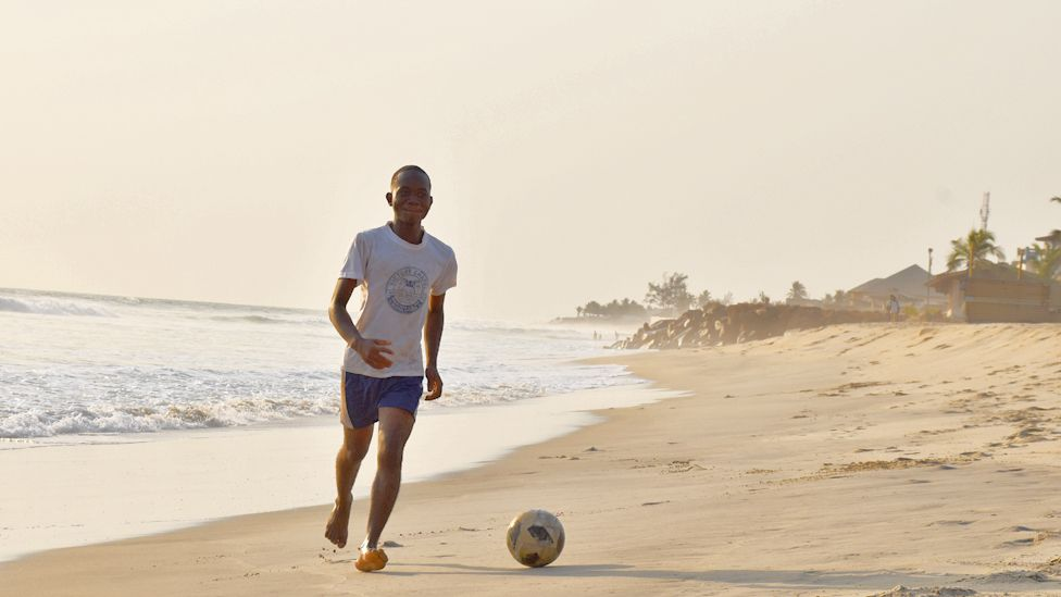 A young man playing football on a beach in Monrovia