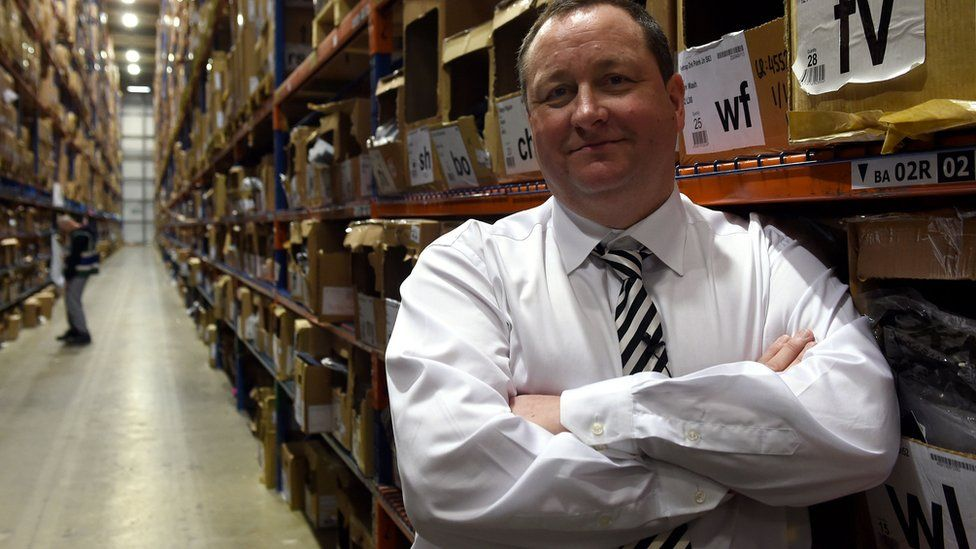 Mike Ashley standing in warehouse aisle