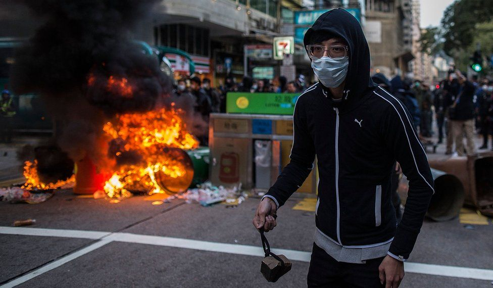 Rioter, about to throw a rock at police
