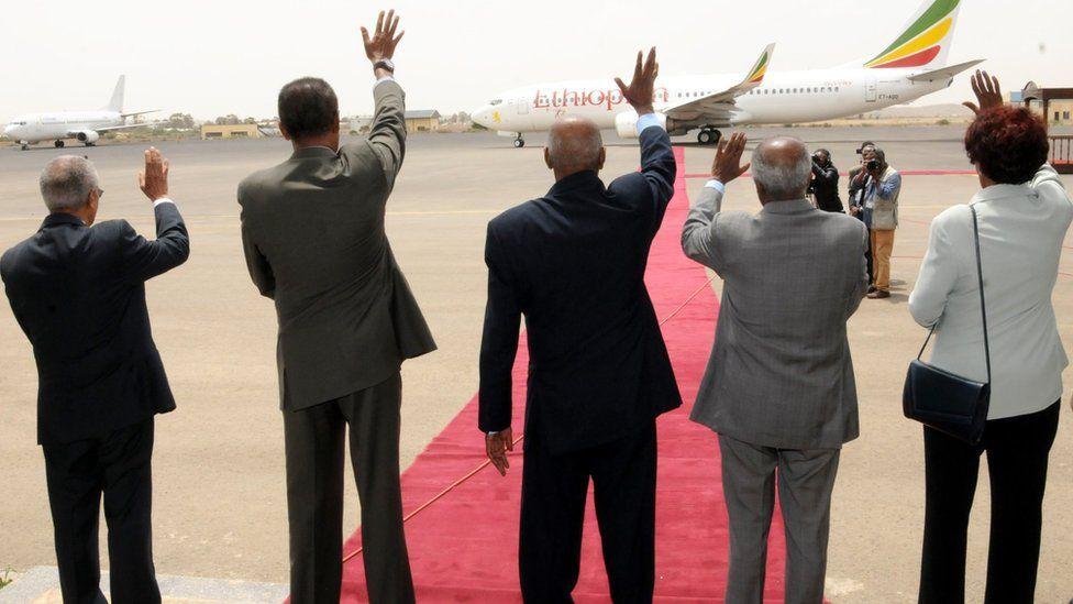 Dignitaries waving farewell to aeroplane