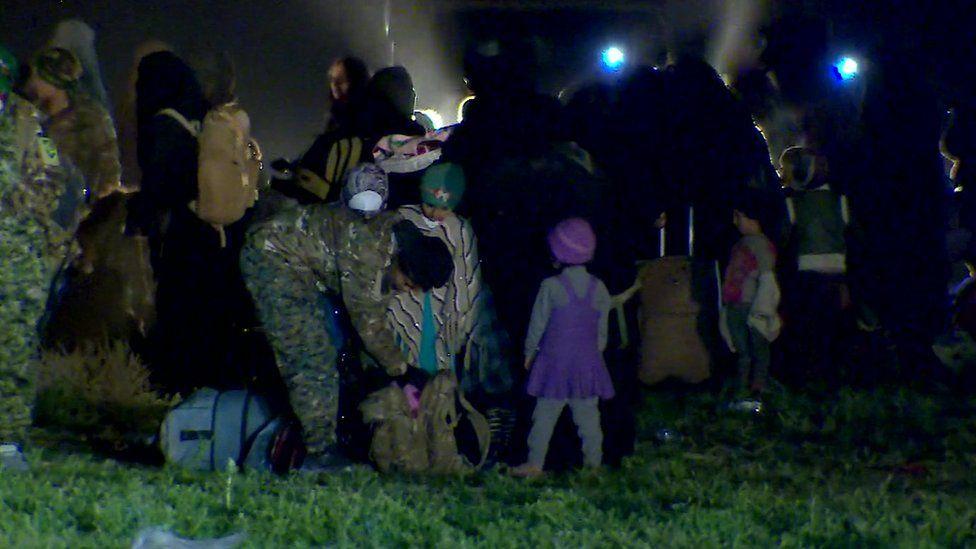 Children and women with their belongings under nightfall