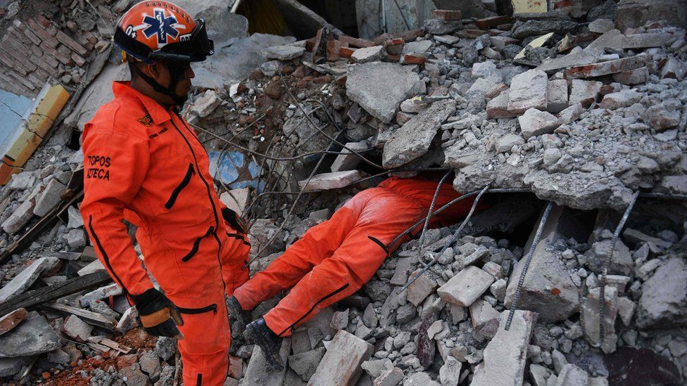Man in jumpsuit with top half of his body under rubble