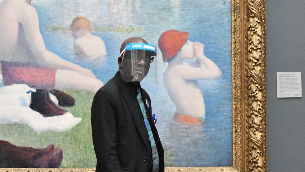 """A member of staff wearing a protective face shield walks past """"Bathers at Asnieres"""" by Georges Seurat inside the National Gallery in July 2020"""