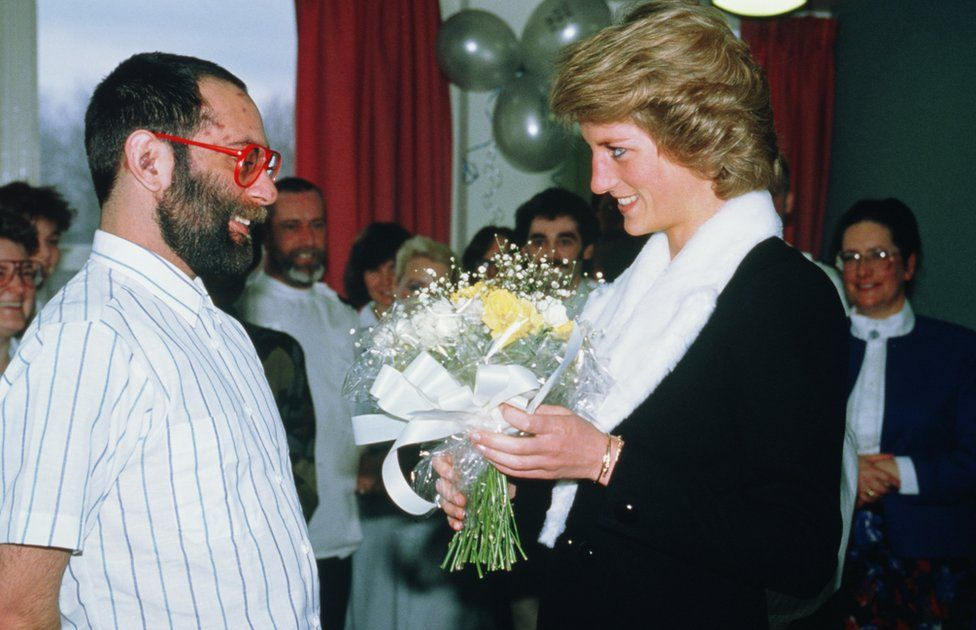 Princess Diana speaks to a patient whilst holding flowers