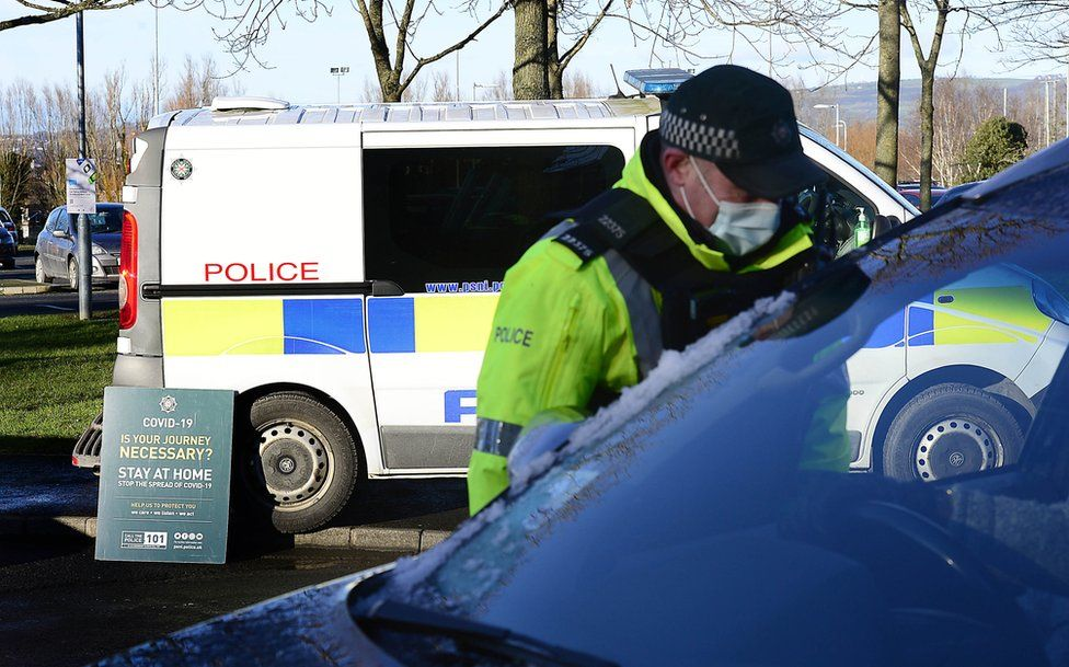 A police officer speaks to the driver of a car