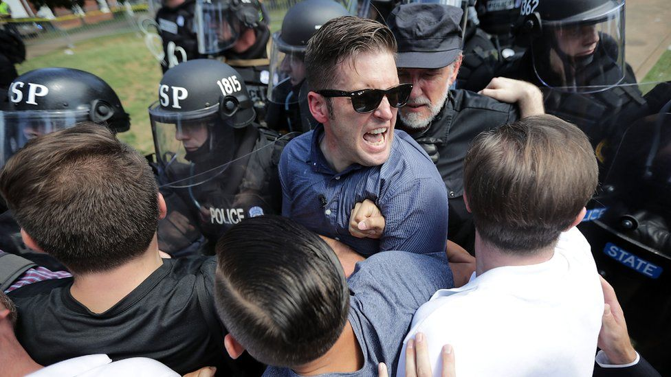 Richard Spencer wears glasses and is tousling with police