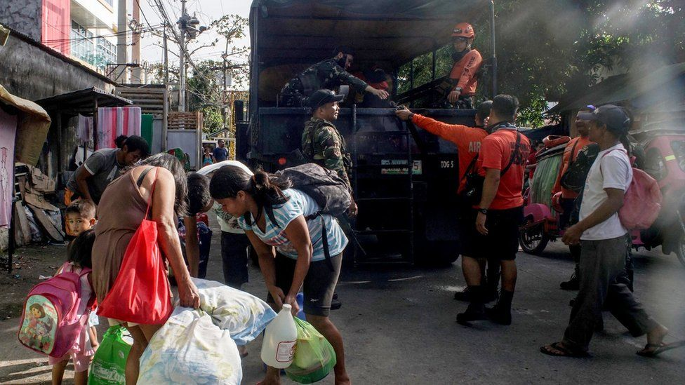 Filipino villagers board a military truck during an evacuation following an eruption of the Mayon Volcano in the town of Camalig, Albay province, Philippines