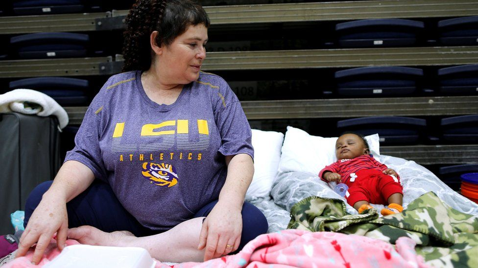 Louisiana evacuee Denise Vital, with her three-month-old godson, says her home was destroyed before, in 2005's Hurricane Rita