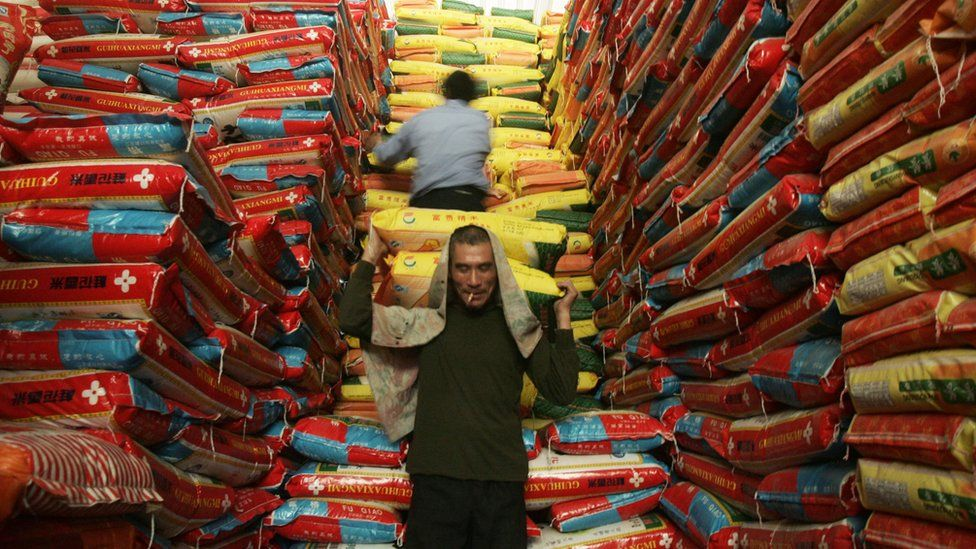 A man carries bags of rice in a warehouse in China.
