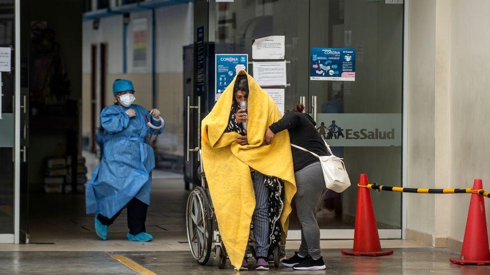 Ein Covid-Patient im Rollstuhl wird am Eingang zu A&E in Peru von einem Arzt begrüßt