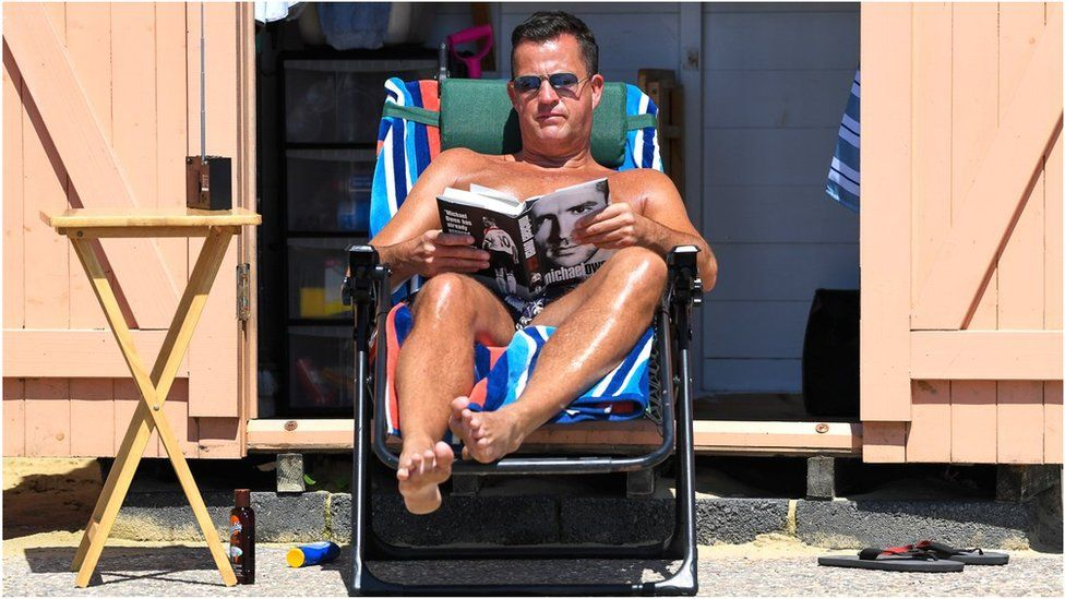 A man reading a book in the sunshine while on holiday