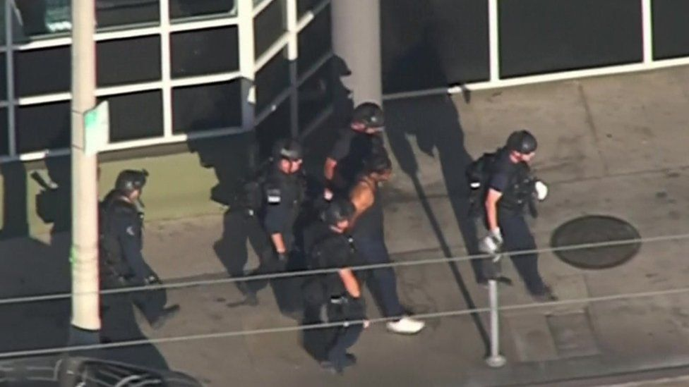 The suspect is led away from the shop by police
