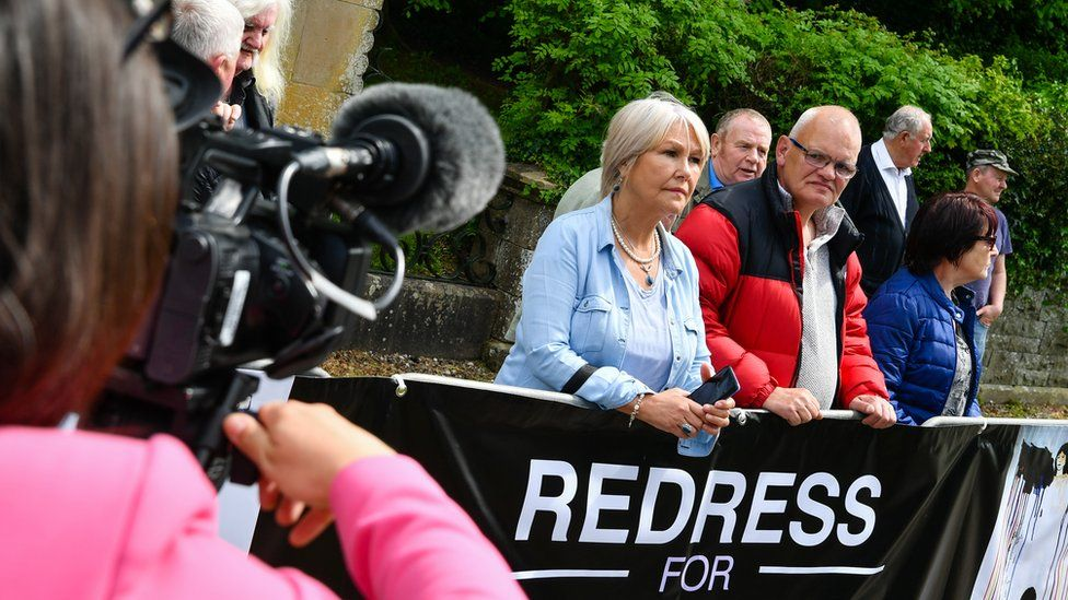 Campaigners protect outside the Northern Ireland secretary's garden party in Enniskillen