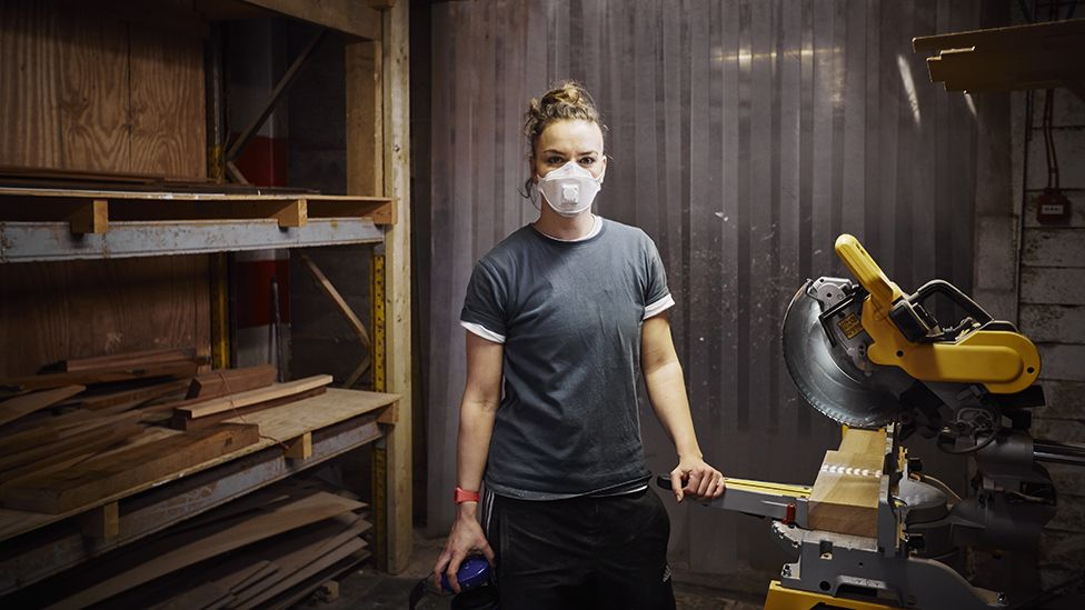 Woman with mask working in carpentry workshop