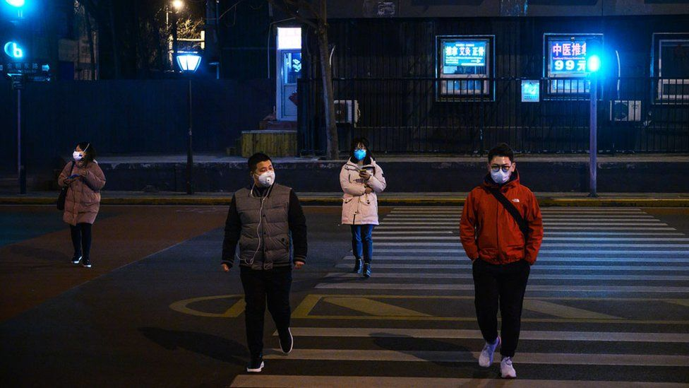 Four people cross the road wearing medical masks in Beijing, China