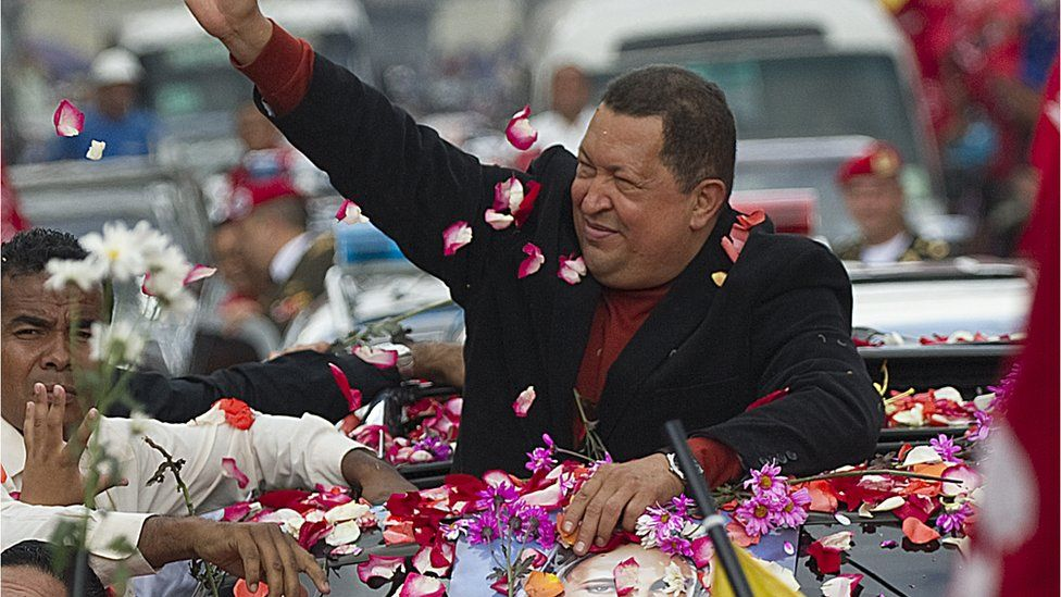 Hugo Chávez is covered in flower petals by supporters as he rides in an open-topped car in 2012.