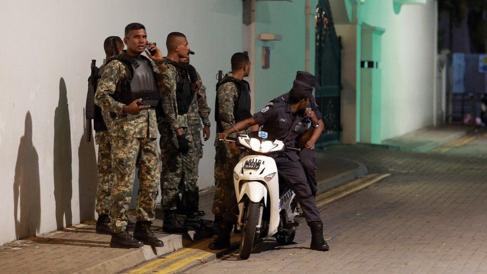 Nov. 2, 2015 photo, Maldivian security officers stand guard near the president's official residence where the military say they found and deactivated an explosive device in Male.
