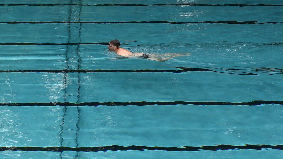 Man swimming in an empty pool