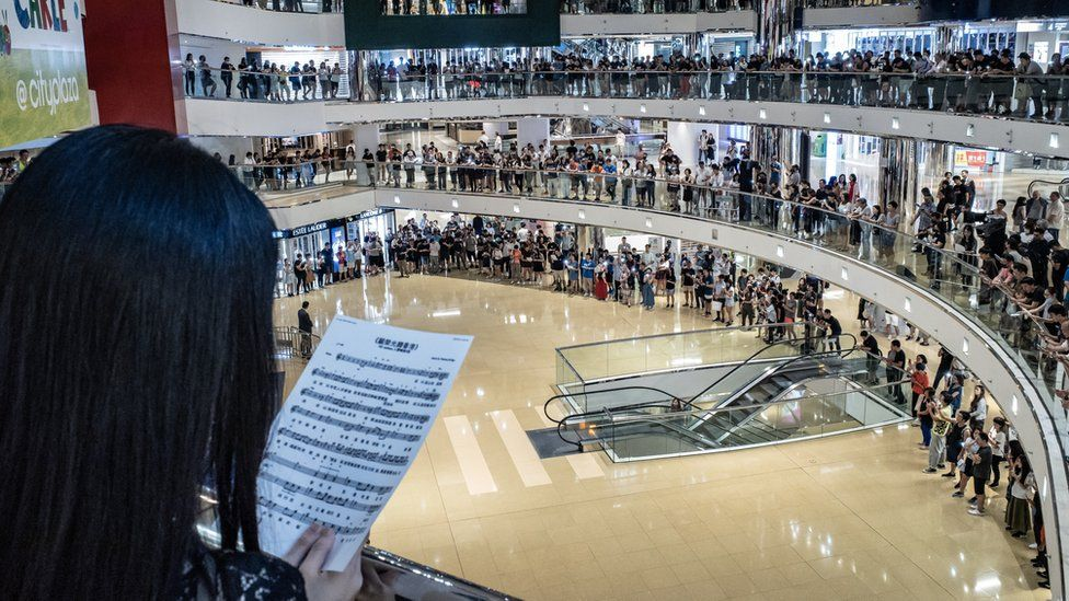 Residents and protesters sing songs and shout slogans as they gather at a shopping mall after business hours in Tai Koo district