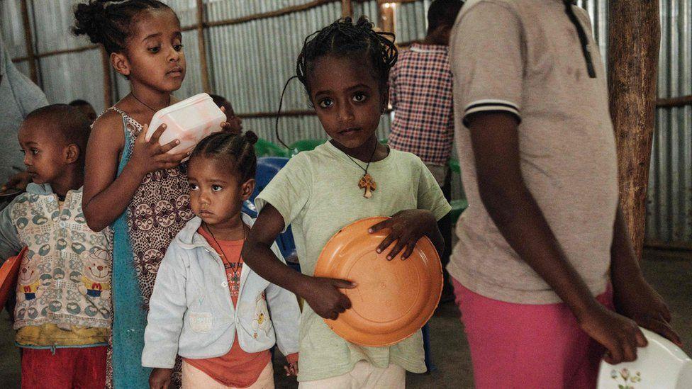 Children, who fled the violence in Ethiopia's, Tigray region, wait in line for breakfast in Mekelle