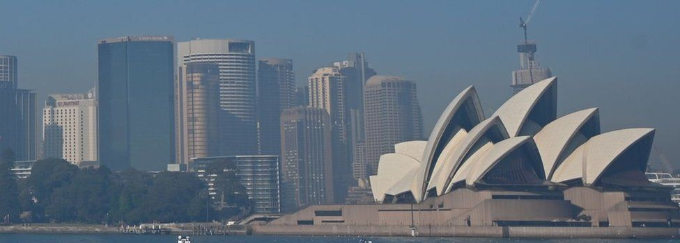 Sydney Opera House and the city skyline seen through a layer of smoke