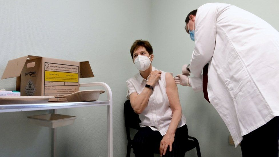 Healthcare worker Adrienne Kertesz receives the first injection nationwide of the Pfizer-BioNTech jab
