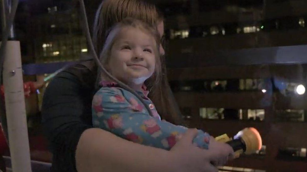 A young girl smiles as she sits on her mum's lap in front of a window from where twinkling lights can be seen down below