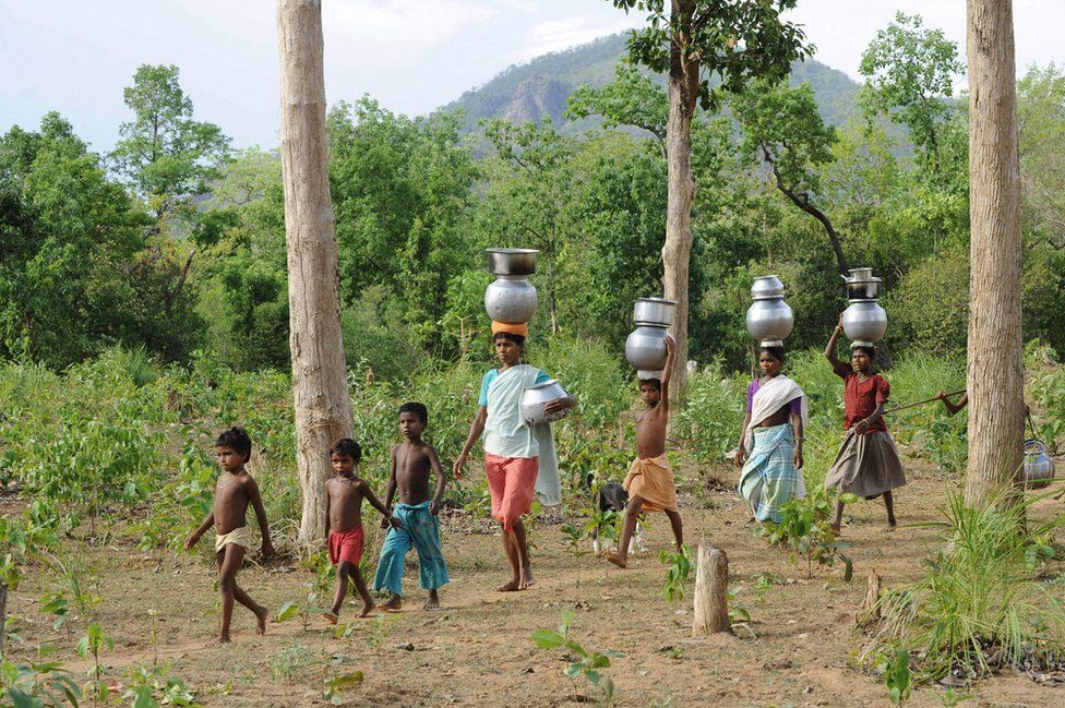 Indian women and children of the Gothikoya or Muria Gond tribe from Maoist insurgency-hit Chhattisgarh state walk 3 km for drinking water from their temporary abodes inside the forest terrain of Khammam district, about 450 km from Hyderabad, on July 2, 2009.
