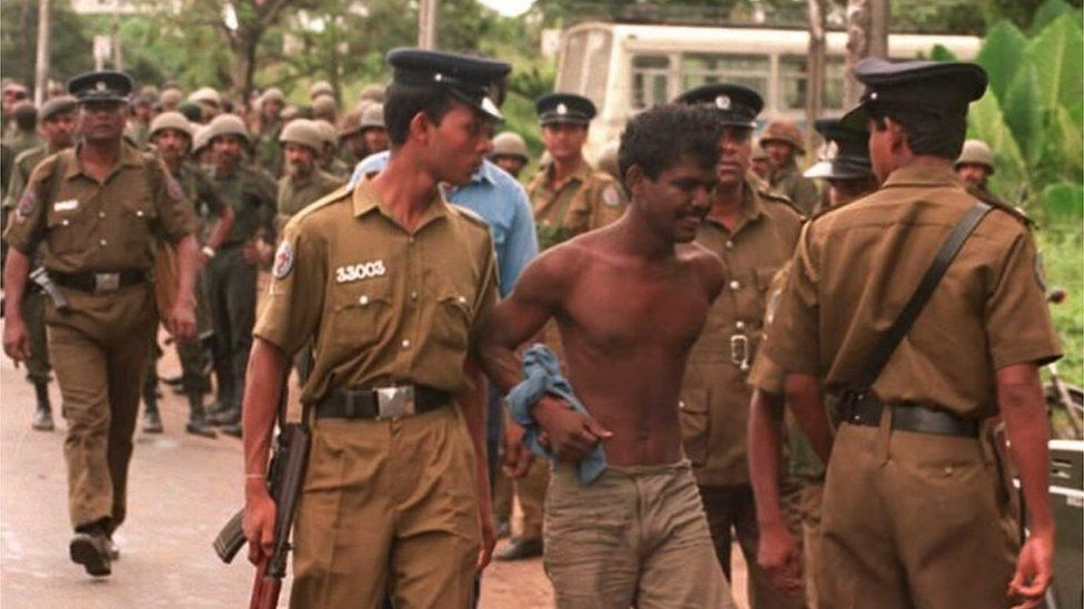Police take into custody a suspected Tamil Tiger guerrilla during a search operation near the Orugodawatte crude oil complex and the nearby Kolonnawa oil tank farm, which were allegedly blown up by suspected Tamil Tiger guerrillas in Colombo 20 October.