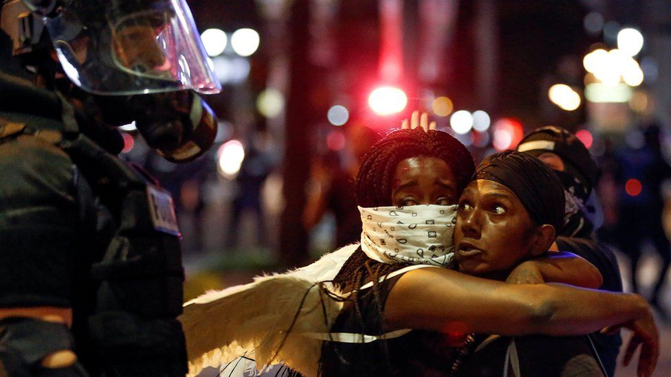 Two women embraced while looking at a police officer in Charlotte, North Carolina during a protest on 21 September