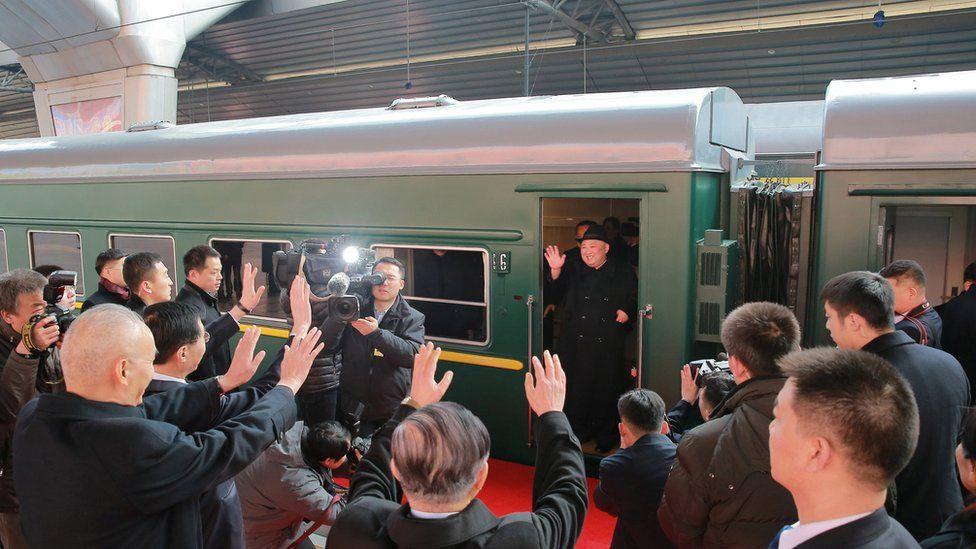 North Korean leader Kim Jong Un waves from a train in Beijing