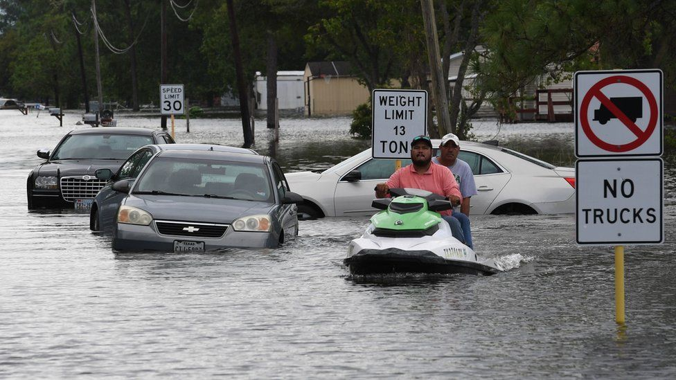 Locals jet ski through the flooded streets in Crosby, Texas, 30 Aug 2017