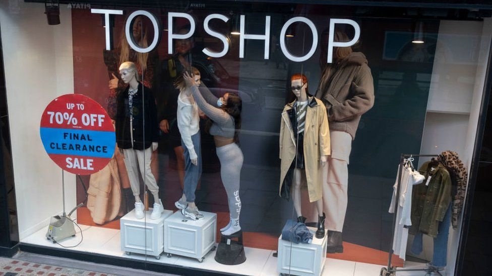 Woman in mask dresses Topshop window