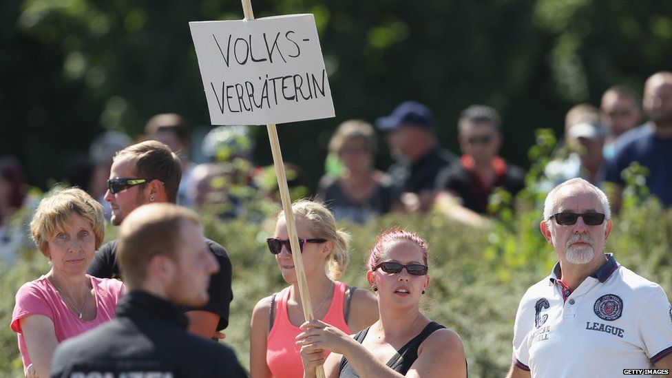 """An onlooker holds a sign that reads """"Nation Traitor"""" during a visit by German Chancellor Angela Merkel to the asylum shelter in Heidenau"""