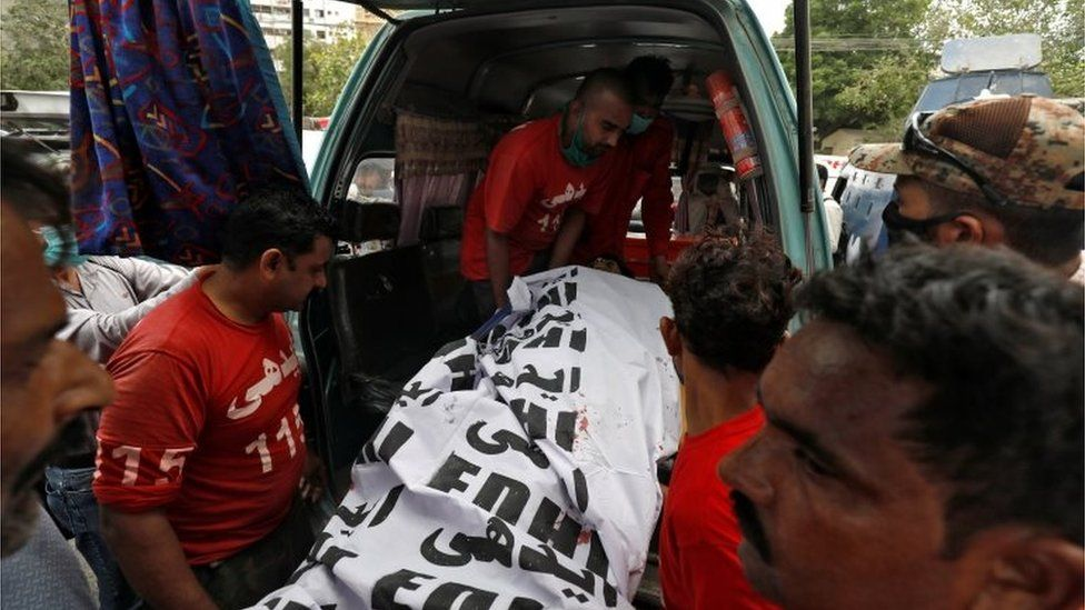 The covered body of a suspected attacker is removed at the site of an attack outside Pakistan Stock Exchange in Karachi June 29, 2020.