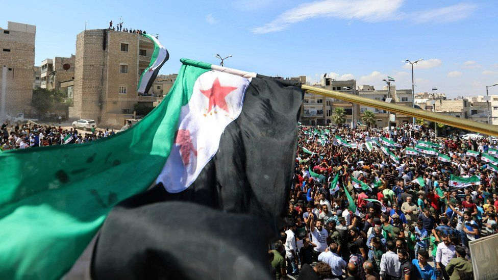 Syrian protesters wave their national flag as they demonstrate against the regime and its ally Russia, in the rebel-held city of Idlib on September 7, 2018
