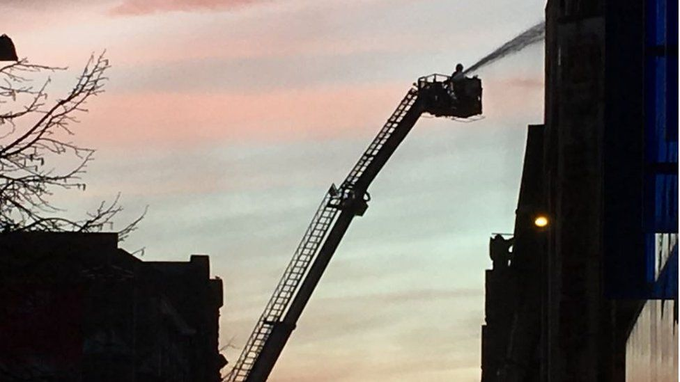 Firefighters dampen down the building