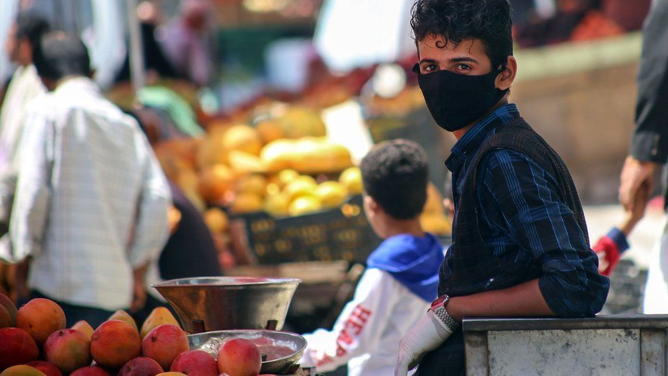 A youth waring a face mask sells fruit at a market in Taiz, Yemen (1 June 2020)