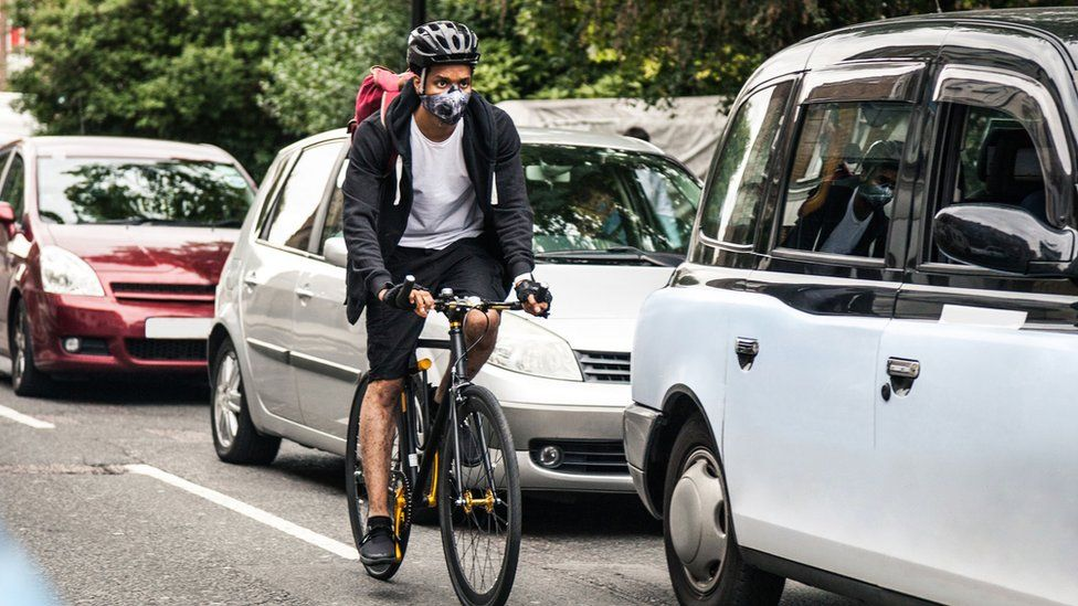 Cyclist riding on street with traffic jam