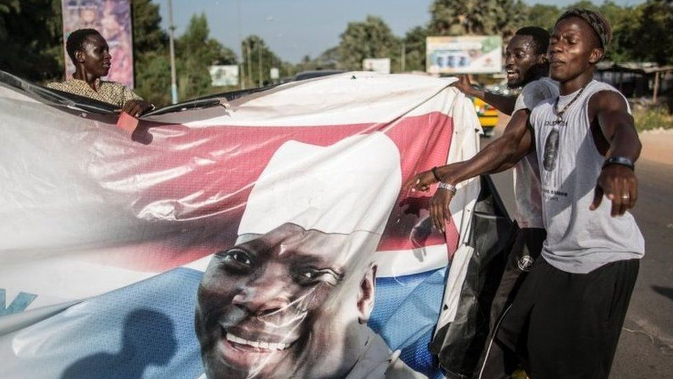 Supporters of the newly elected Gambia President Adama Barrow tear down posters of the incumbent Yahya Jammeh in Serekunda on 2 December 2016.
