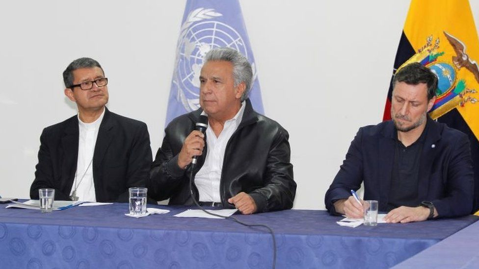 President Lenin Moreno (C) addresses the audience next to Catholic Bishop Luis Cabrera (L) and Arnaud Peral, representative of the United Nations in Ecuador, in a meeting with the leaders of indigenous communities.