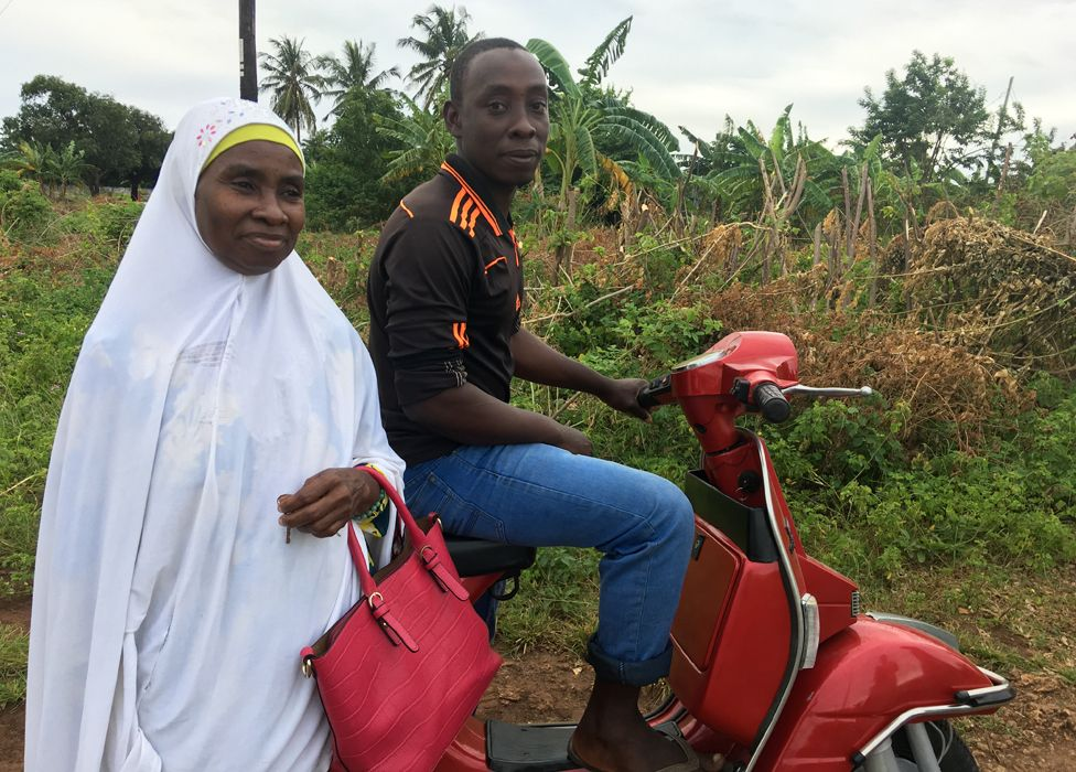 Safia and her son on the scooter she bought