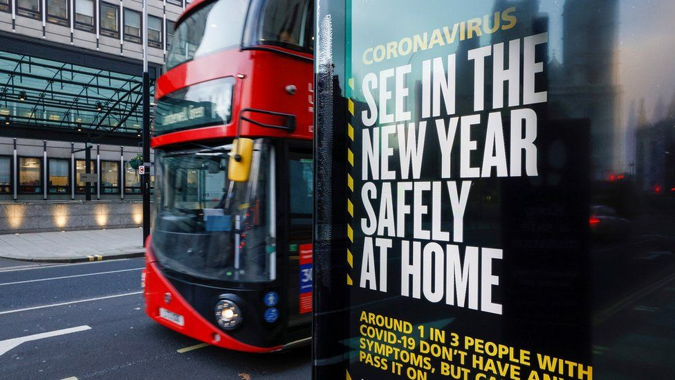A bus drives past a British governments advertisement sign reminding people to stay at home in the New Year, near the Houses of Parliament, in London