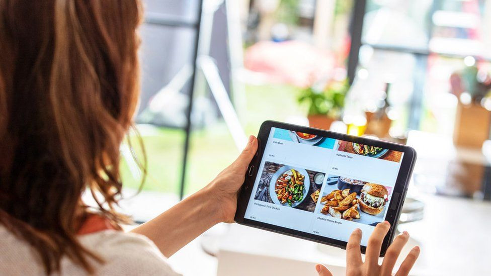 A woman looking at the HelloFresh app on a tablet