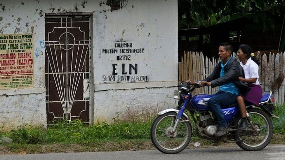 A couple ride a motorcycle past a graffiti of the ELN (National Liberation Army of Colombia) guerrillas on a wall in El Palo, department of Cauca, Colombia, on March 15, 2016.