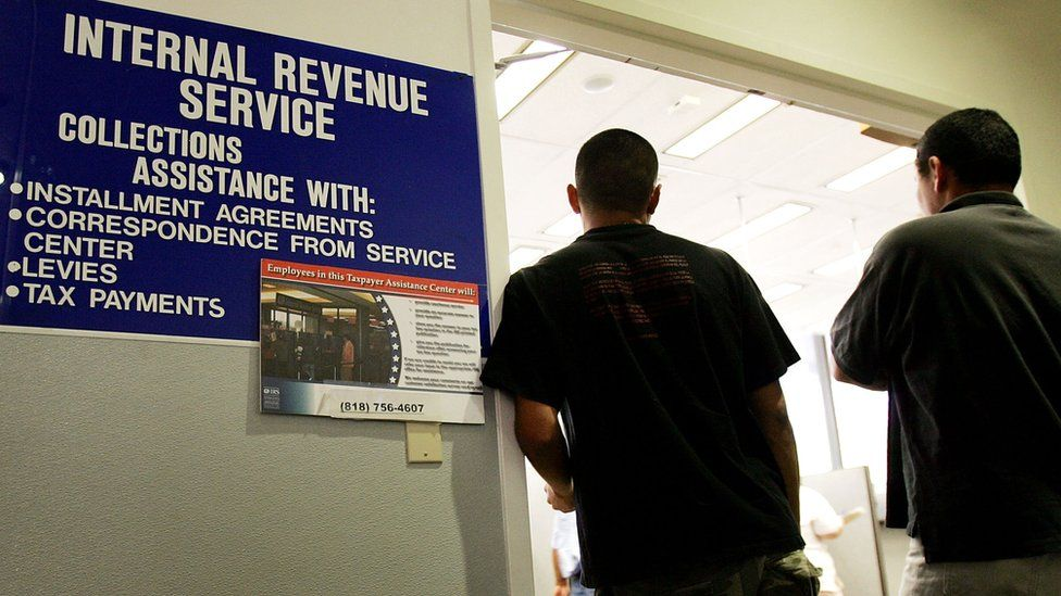 People stand at the door of a local Internal Revenue Service (IRS) office